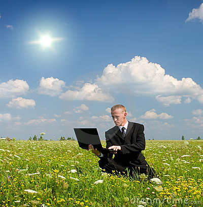 Businessman from notebook on meadow