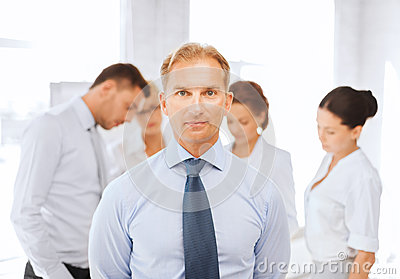 Businessman in office with group on the back
