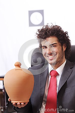 Businessman in the office with moneybox