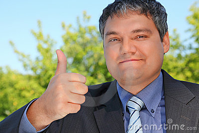 Businessman outdoor in summer with ok gesture