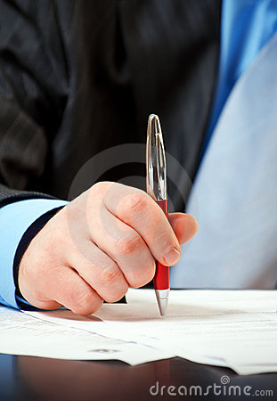 Businessman with pen signing contract