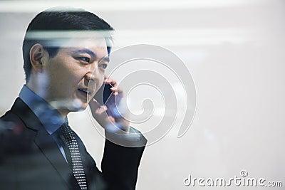Businessman on the phone in parking garage, looking through window