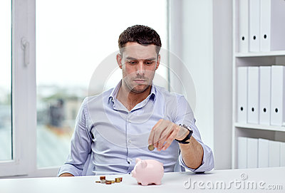 Businessman With Piggy Bank And Coins At Office Stock ...