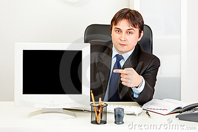 Businessman pointing at monitor with blank screen
