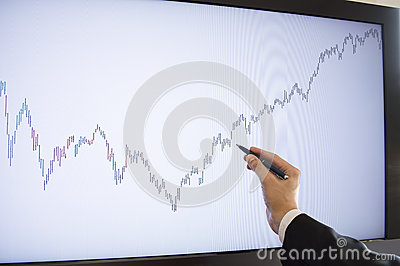 Businessman pointing with pen on the monitor