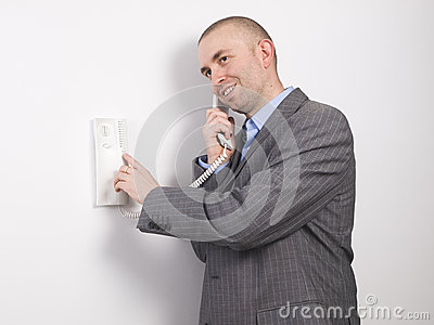 Businessman pressing an intercom