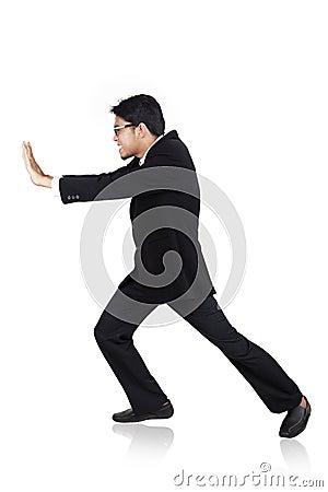 Businessman pushing something heavy pose