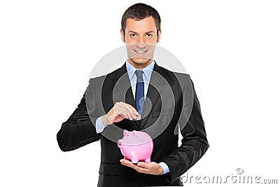 Businessman putting a coin into a piggy bank
