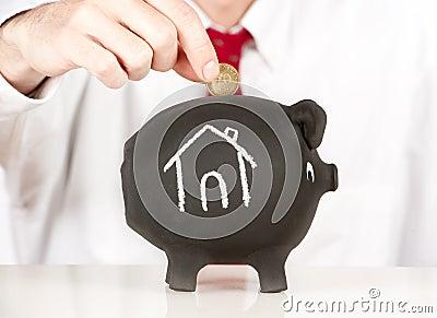 Businessman putting money on a piggy bank