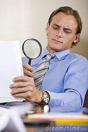 Businessman reading fine print in contract