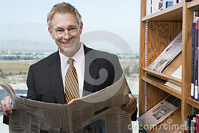 Businessman Reading Newspaper In Library