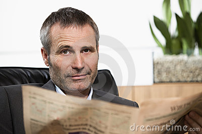 Businessman reading newspaper looking straight.