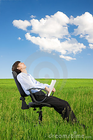 Businessman relaxing on grassland under blue sky