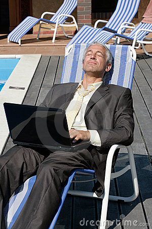 Businessman resting on deck chair
