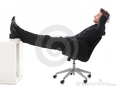 Businessman resting in office with legs on desk