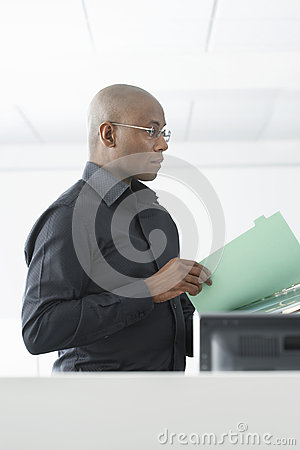 Businessman Reviewing File At Computer Desk