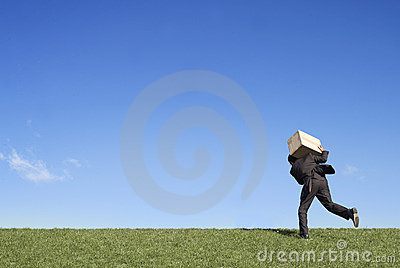 Businessman running with box