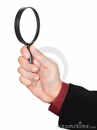 Businessman s hand holding magnifying glass