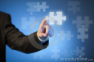 Businessman s hand touching abstract puzzle piece