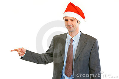 Businessman in Santa hat pointing at copy space