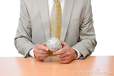 Businessman Seated at Desk With Ball of Money