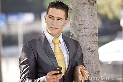 Businessman sending messages at the cellular