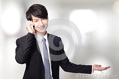 Businessman showing copy space with phone