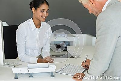 Businessman signing employee sheet Stock Photo