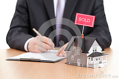 Businessman signs contract behind home model