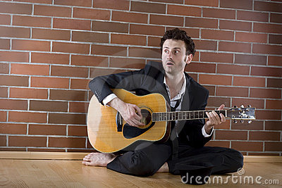 Businessman sits singing with guitar on the floor