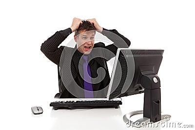 Businessman sitting behind desk is in despair