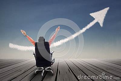 Businessman sitting on chair with raised arms and up arrow sign
