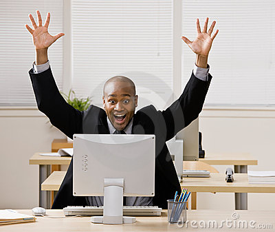 Businessman sitting at desk cheering