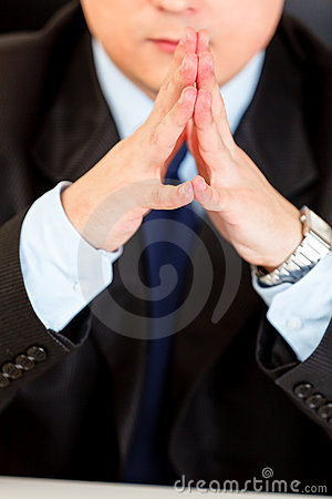 Businessman sitting at desk. Close-up on hands.