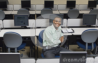 Businessman Sitting At Desk In Computer Room