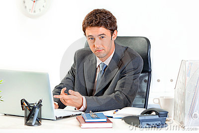 Businessman sitting at desk and pointing on laptop