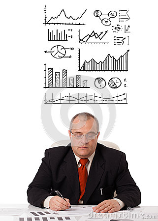 Businessman sitting at desk with statistics