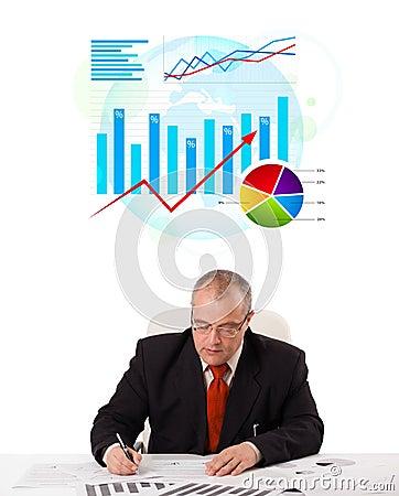 Businessman sitting at desk with statistics
