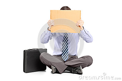 Businessman sitting on ground and hiding his face with a piece o
