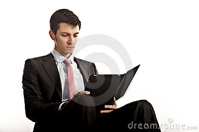 Businessman sitting and reading computer tablet