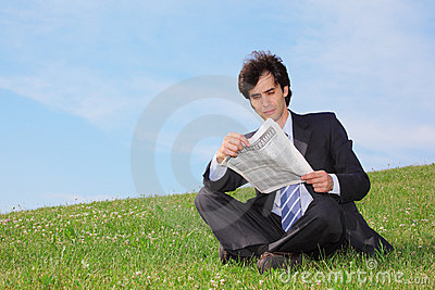 Businessman sitting and reading newspaper
