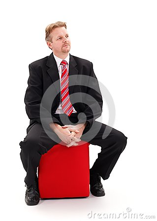 Businessman sitting on red tabouret
