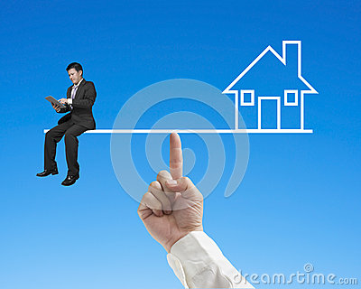 Businessman sitting on seesaw with home balance by index finger