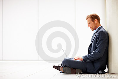 Businessman sitting and using laptop on floor