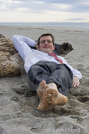 Businessman sleeping on a beach
