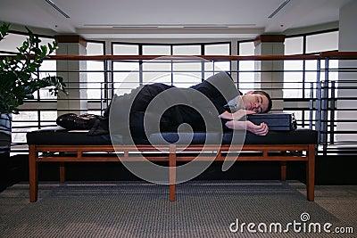 Businessman Sleeping in Hallway