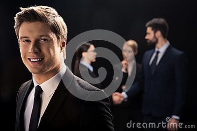 Businessman smiling on foreground while business people connecting behind Stock Photo