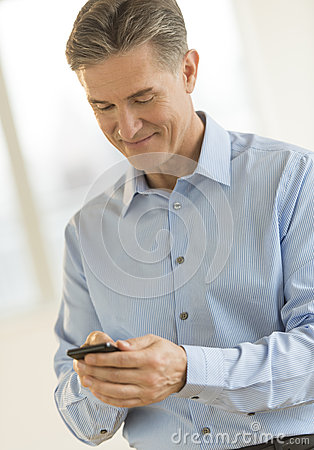 Businessman Smiling While Text Messaging Through Smart Phone