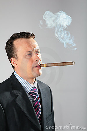 Businessman smokes  cigar