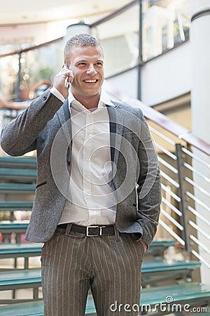 Businessman speaking on smartphone in business building